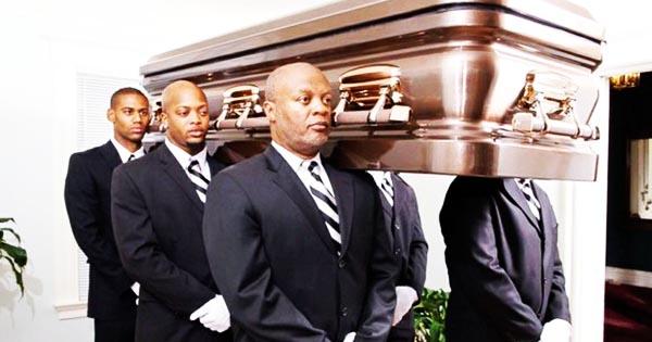 African American men carrying casket at funeral