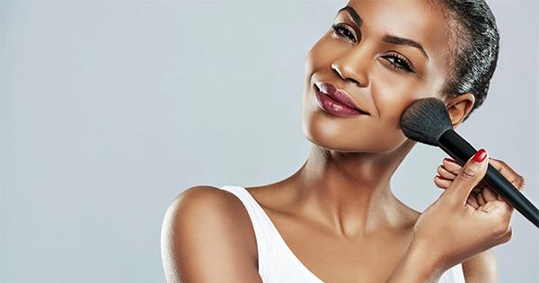 Black woman putting on makeup