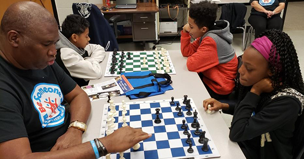 Orrin Hudson, founder of Be Someone, teaching children how to play chess