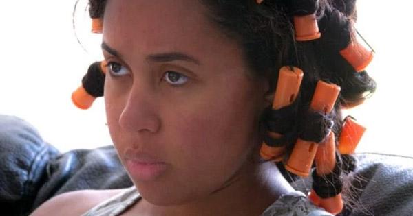 Black woman wearing hair rollers